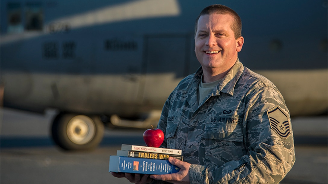Air Force Master Sgt. Jason Paseur, the 386th Air Expeditionary Wing historian, poses for a photo in front of a C-130H Hercules aircraft