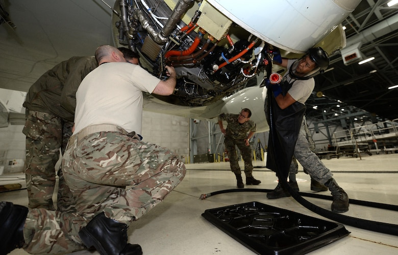 U. S. Air Force Senior Airman Roland Robicheaux Jr., a hydraulic technician from the 55th Aircraft Maintenance Squadron, hooks up an external hydraulic pressure test unit alongside Royal Air Force 51 Squadron maintenance personnel while troubleshooting landing gear problems on a RAF RC-135 Airseeker, suspended by 30 ton aircraft jacks inside a hangar at Offutt Air Force Base, Neb. Feb. 12. The aircraft diverted from Nellis Air Force Base to Offutt where it received maintenance assistance from the 55th MXG to correct a landing gear problem that occurred while participating in a joint exercise. (U.S. Air Force photo by Delanie Stafford)