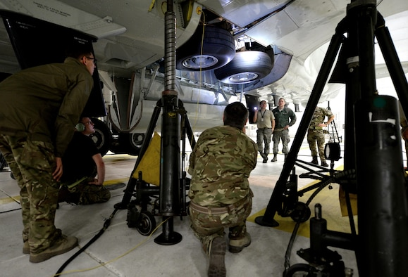 Royal Air Force 51 Squadron and 55th Maintenance Squadron maintenance personnel troubleshoot landing gear problems on a RAF RC-135 Airseeker suspended by 30 ton aircraft jacks inside a hangar at Offutt Air Force Base, Neb. Feb. 12. The aircraft diverted from Nellis Air Force Base to Offutt where it received maintenance assistance from the 55th MXG to correct a landing gear problem that occurred while participating in a joint exercise. (U.S. Air Force photo by Delanie Stafford)