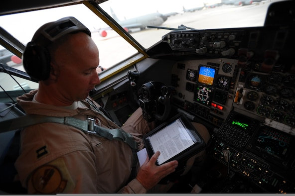 U.S. Air Force Capt. Brett Pierson, a pilot with the 340th Expeditionary Air Refueling Squadron, refers to his personal computer tablet during preflight checks aboard a KC-135 Stratotanker aircraft bound for a refueling mission in Afghanistan May 8, 2011, in support of Operation Enduring Freedom. The Hanscom Collaboration and Innovation Center at Hanscom AFB, Mass., is working with industry to provide Air Mobility Command pilots with hardened digital tablets, which can withstand digital attack and electronic interference during flight, replacing hundreds of pages of printed material with secure electronic flight bags. This acquisition method, known as a plug-test can quickly put needed tools in the hands of warfighters, before the technology is outdated. (U.S. Air Force Photo/Master Sgt. William Greer)