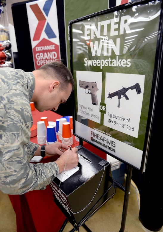 Capt. Hawkins Thomas, Air Force Reserve Officer Training Corps field trainer, completes an entry form during the grand opening of the firearms counter at the Maxwell Base Exchange, Friday, Feb. 17, 2017. The winners of the raffle will be chosen within a week. (U.S. Air Force photo/Senior Airman Tammie Ramsouer)
