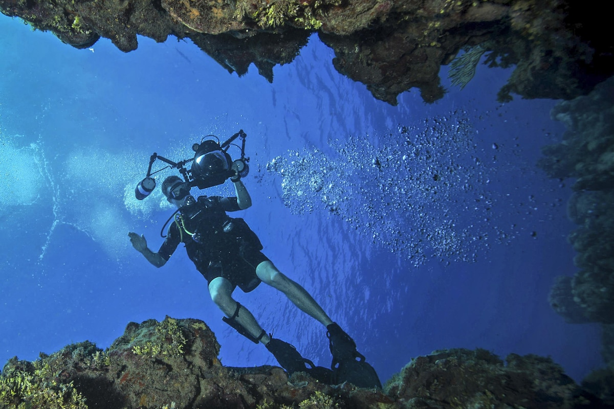 A sailor trains underwater with a camera.