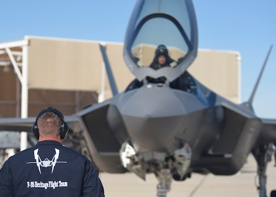An F-35 Lightning II maintainer stands by to marshal Maj. Will Andreotta, 61st Fighter Squadron F-35 hertage flight pilot, during the Heritage Flight Training and Certification Course Feb. 10, 2017, at Davis-Monthan Air Force Base, Ariz. Heritage and demonstration teams need to be certified annually to participate in open houses and air shows worldwide. (U.S. Air Force photo by Senior Airman James Hensley)