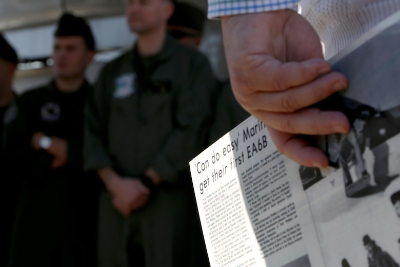 An attendee holds a copy of a news article depicting the arrival of the first EA-6B Prowler into the Marine Corps during a 40th anniversary commemoration ceremony held aboard Marine Corps Air Station Cherry Point, N.C., Feb. 17, 2017. The Prowler provides an umbrella of protection for strike aircraft, ground troops and ships by jamming enemy radar, electronic data links and communications. The Marine Corps is transitioning from the Prowler to the F-35B Lightning II. (U.S. Marine Corps photo by Cpl. Jason Jimenez/ Released)