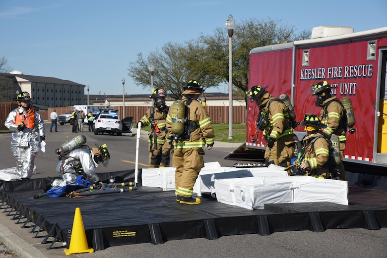 """Members of the 81st Infrastructure Division fire department set up a decontamination site for affected """"victims"""" during a train derailment exercise Feb. 16, 2017, on Keesler Air Force Base, Miss. The exercise scenario simulated a train and vehicle collision, which resulted in a derailment and chemical spill, creating a mass casualty and HAZMAT response event. This exercise tested base and local civilian emergency response organizations' ability to operate in a multi-agency and multi-jurisdiction crisis situation. (U.S. Air Force photo by Kemberly Groue)"""