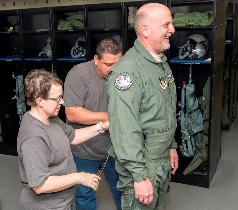 – April Fisher (L) and Eddie Scribner (C) flight equipment life support technicians with the 559 Flying Squadron at Joint Base San Antonio-Randolph, Texas, put the finishing touches on a G-suit for John Fedrico, deputy assistant Secretary of the Air Force for  Reserve Affairs and Airman Readiness in preparation for a T-6 orientation flight here Feb. 13. Fedrico's visit, hosted by the 340 FTG, served a dual purpose. Fedrico presented a letter of thanks to one of the unit's own, retired Air Force Lt. Col. Todd Ernst. Ernst was honored for his efforts to help ensure families of Reserve and Guard service members receive the same survivor benefits as active duty service members. Fedrico also received a mission brief and got to experience the unit's operations first hand. (Air Force photo by Sean Worrell, Joint Base San Antonio-Randolph Public Affairs)