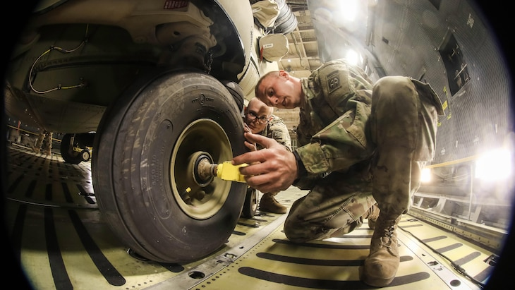 A soldier unlocks a CH-47F Chinook wheel before moving the helicopter off a C-5M Super Galaxy aircraft at Pope Field, N.C., Feb. 14, 2017. Army photo by Capt. Adan Cazarez