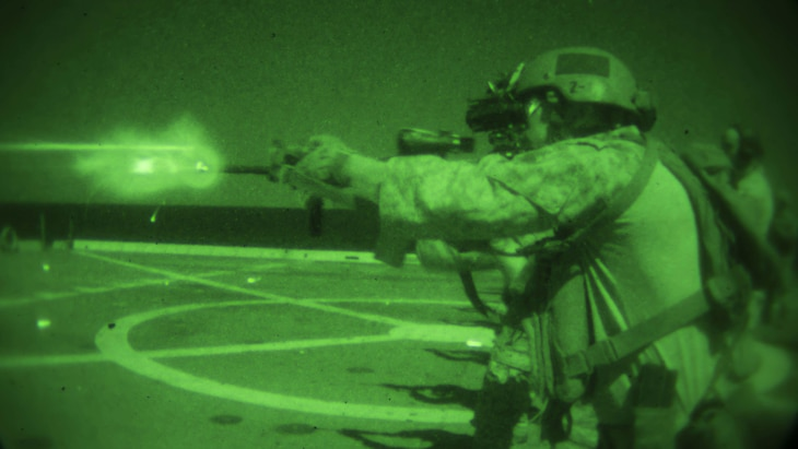 As seen through a night-vision device, Marines and sailors use infrared lasers to sight in on targets during training aboard the USS Somerset, Feb. 10, 2017. Marine Corps photo by Cpl. April Price