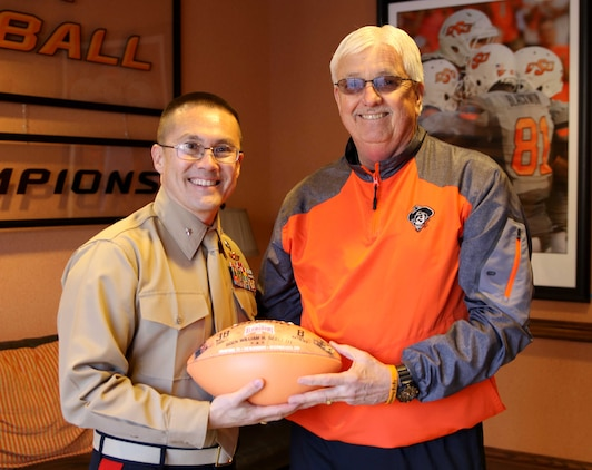 U.S. Marine Corps Director of Intelligence, Brig. Gen. William H. Seely III, poses with Mack Butler, director of football operations at Oklahoma State University, after being presented with a football, Feb 15. Seely visited OSU to speak to Marine Corps officer candidates and deliver a motivational speech to the wrestling team ahead of their National Championship Sunday.