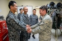 Japan Air Self-Defense Force Airman 1st Class Nobuhiro Kamikiharo, maintenance crew specialist from Tsuiki Air Base, Japan, and U.S. Air Force Airman 1st Class Jesse Inman, 18th Operations Support Squadron aircrew flight equipment apprentice, shake hands Feb. 17, 2017, at Andersen Air Force Base, Guam. Aircrew flight equipment Airmen from both nations are working under the same roof, where they can learn customs from each other's culture and compare techniques of one another's craft. (U.S. Air Force photo by Senior Airman John Linzmeier/released)
