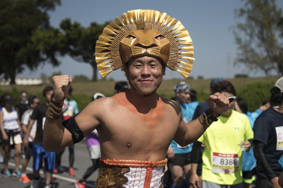 A costumed runner smiles as he's cheered on through a portion of the Okinawa Marathon Feb. 19, 2017, at Kadena Air Base, Japan. Kadena AB has supported and strengthened relations with the local community through the Okinawa Marathon for the last 25 years. (U.S. Air Force photo by Staff Sgt. Peter Reft/Released)