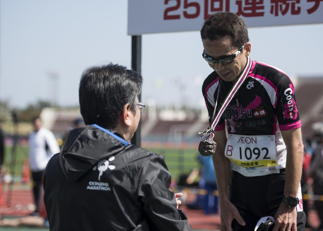 Masanao Ishihara, Okinawan veteran marathoner, receives a commemorative medal, during the 25th annual Okinawa Marathon Feb. 19, 2017, at the Okinawa Prefectural Comprehensive Park in Okinawa, Japan. Commemorative medals were given out to participants who raced and completed the marathon. (U.S. Air Force photo by Senior Airman Omari Bernard/Released)
