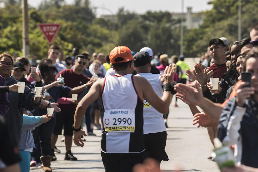 Okinawa Marathon runners high five volunteers and supporters along the route on Kadena Feb. 19, 2017, at Kadena Air Base, Japan. Approximately 500 U.S. military members and families came out to support the runners as they made their way through the base. (U.S. Air Force photo by Airman 1st Class Corey Pettis/Released)