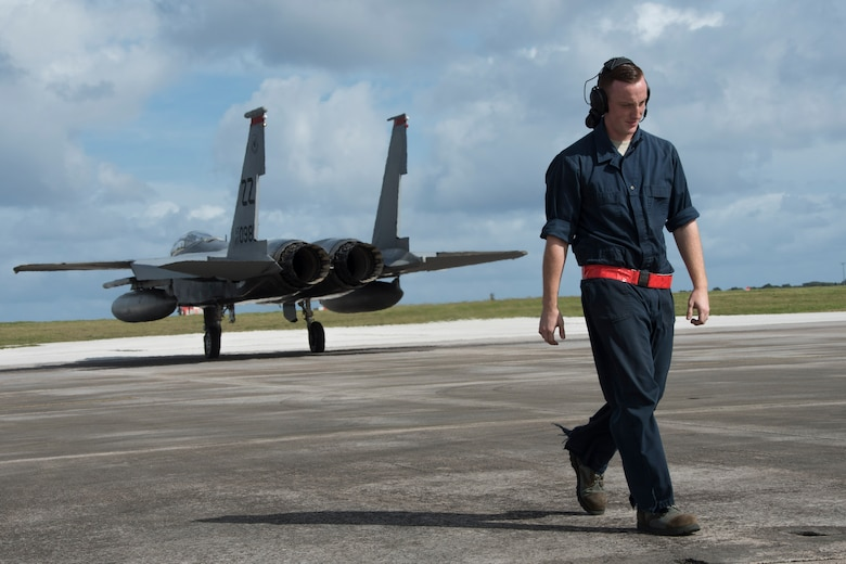 U.S. Air Force Airman 1st Class Dennis Hatcher, 67th Aircraft Maintenance Unit crew chief, steps away from an F-15 Eagle from the 67th Fighter Squadron after marshaling it out to the taxiway during annual exercise Cope North Feb. 20, 2017, at Andersen Air Force Base, Guam. Through training exercises such as Cope North, the U.S., Japan and Australian air forces develop combat capabilities, enhancing air superiority, electronic warfare, air interdiction, tactical airlift and aerial refueling. (U.S. Air Force photo by Senior Airman John Linzmeier/released)