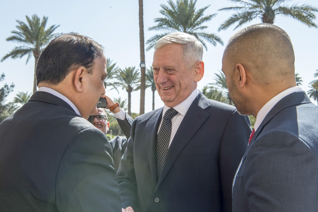 Defense Secretary Jim Mattis, center, shakes hands with Iraqi Minister of Defense Arfan al-Hayali at the Ministry of Defense in Baghdad, Iraq