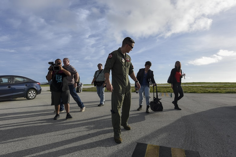 U.S. Air Force Capt. Brian Navin, 909th Air Refueling Squadron pilot, guides reporters toward an aircraft Feb. 21, 2017, at Andersen Air Force Base, Guam. Media teams visited Andersen to observe Cope North, an annual exercise designed to increase interoperability between the U.S., Japan and Australian air forces. The 909th ARS provided a flight for the visitors aboard a KC-135 Stratotanker for an observation of air-refueling operations. (U.S. Air Force photo by Senior Airman John Linzmeier/released)