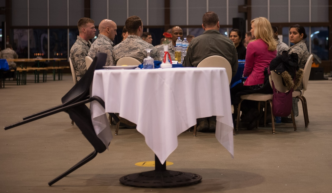 A POW/MIA table sits in front of a crowd during the 2016 Maintenance and Logistics Airmen Annual Award Ceremony on Ramstein Air Base, Germany, Feb. 17, 2017. Also known as the missing man table, the setup is used in military dining facilities of the U.S. armed forces and during special occasions to commemorate the fallen, missing, or imprisoned service members. It originated out of U.S. concern of the Vietnam War's large POW/MIA numbers. (U.S. Air Force photo by Senior Airman Lane T. Plummer)