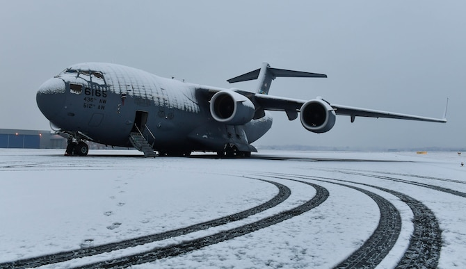 A C-17 Globemaster III is covered in snow in Cologne, Germany, Feb 11, 2017. A 721st Aircraft Maintenance Squadron maintenance recovery team was sent from Ramstein Air Base to fix a number four main fuel tank leak on the aircraft. The leak dripped fuel behind the number four engine exhaust, preventing the crew from flying until it was fixed. (U.S Air Force photo by Senior Airman Tryphena Mayhugh)