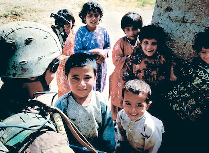 A Marine interacts with children overseas. Likely, his success in another culture can be attributed to Marine Corp Univiserity's CAOCL program.