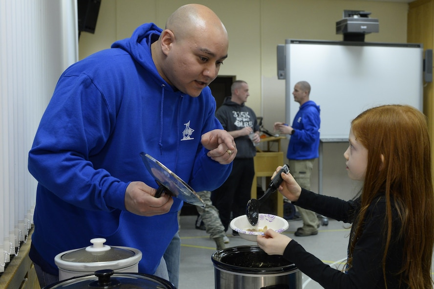 Master Sgt. Benjamin Hill, 52nd Fighter Wing Staff Agencies first sergeant, talks with Liberty Cushing, daughter of deployed Tech. Sgt. Ryan Cushing, as she gets chili during a chili cook-off sponsored by the First Sergeants Association for deployed family night at Spangdahlem Air Base, Germany, Feb. 16, 2017. The Airman and Family Readiness Center holds a deployed family night monthly and different agencies and squadrons take turns sponsoring. (U.S. Air Force photo by Tech. Sgt. Staci Miller)