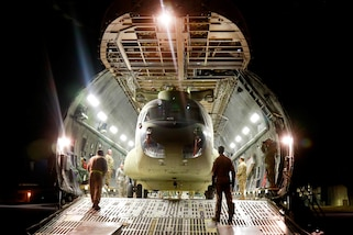 Soldiers and airmen prepare to move a CH-47F Chinook helicopter into position before exiting the cargo bay of a C-5M Super Galaxy at Pope Army Airfield, Fort Bragg, N.C., Feb. 14, 2017. The soldiers are assigned to the 82nd Airborne Division's 82nd Combat Aviation Brigade. Army photo by Capt. Adan Cazarez