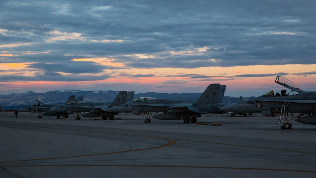 """Several F/A-18C Hornets with Marine Fighter Attack Squadron (VMFA) 323 """"Death Rattlers"""" rest on the flight line prior to night operations at Naval Air Station Fallon, Nev., Feb. 15. The Death Rattlers, one of two Marine Hornet squadrons to deploy aboard Navy aircraft carriers, trained at NAS Fallon to strengthen tactical air integration, fulfill predeployment requirements and build rapport with the Navy squadrons they will deploy with in summer 2017. (U.S. Marine Corps photo by Sgt. Lillian Stephens/Released)"""