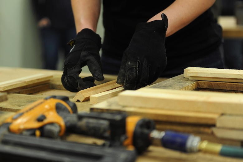 A Service Member Measures Wood For A Picture Frame Before Nailing The  Pieces Together During A