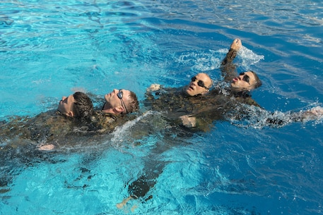 "Marines with Headquarters and Headquarters Squadron swim in a ""dragon boat"" formation at the combat training tank during the Grizzly Challenge at Marine Corps Air Station Miramar, Calif., Feb. 14. The challenge is held quarterly to bring the Marines in the unit together for team building. (U.S. Marine Corps photo by Lance Cpl. Liah Kitchen/Released)"