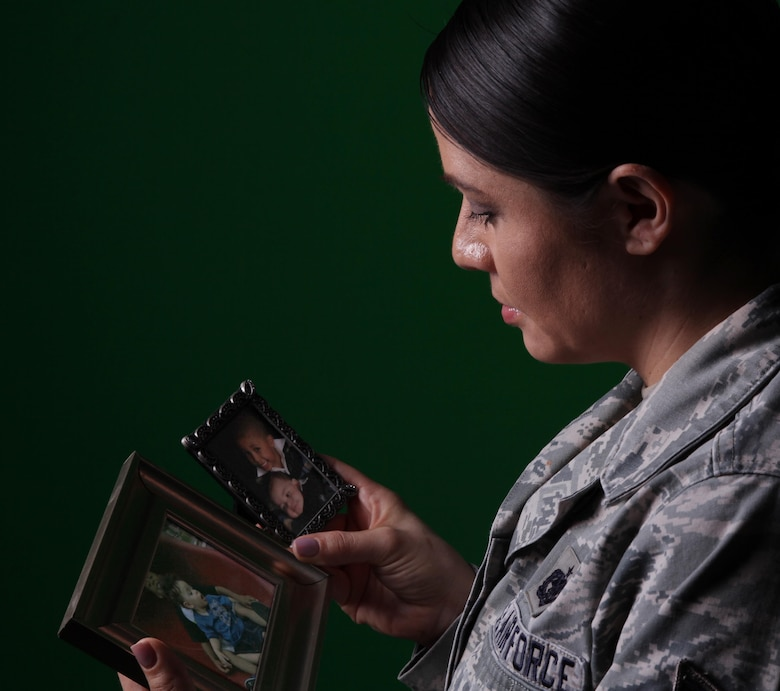 Tech. Sgt. Amee Espinoza, Personnel Customer Service Manager for the ARPC Total Force Service Center, looks at photos of her sons. Espinoza lost her youngest son, but turned the tragedy into therapy and found her calling to serve others through counseling. She completed more than 600 hours of direct and indirect counseling services with individuals and groups focused on DUI and DWIs, addiction, domestic violence, conflict resolution, and anger management and was chosen as the Air Force Reserve Command nomination for the 2016 GEICO Military Service Award. (U.S. Air Force photo by Quinn Jacobson)