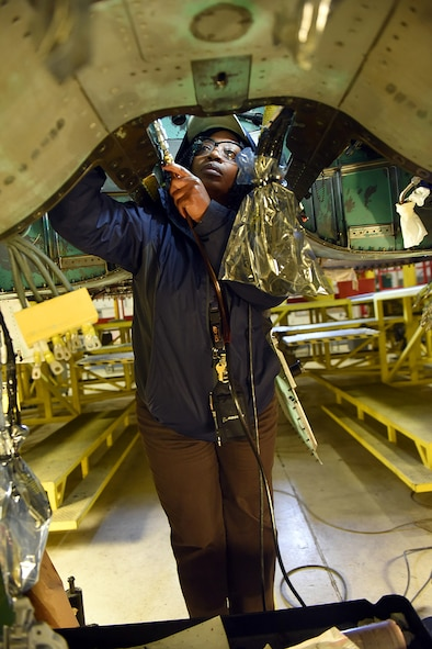 Tanya Thompson, 561st Aircraft Maintenance Squadron aircraft worker installs hydraulic lines in the airframe mounted accessory drive area of an F-15 during depot maintenance Feb. 16, 2017, at Robins Air Force Base. (U.S. Air Force photo by Tommie Horton/Released)