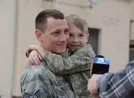 Senior Airman Kevin Teague of the 507th Aircraft Maintenance Squadron holds his son, Aiden, while being interviewed by local media following a deployment Feb. 19, 2017, at Tinker Air Force Base, Okla. More than 90 Reservists deployed in December 2016 in support of air operations at Incirlik Air Base, Turkey, against the Islamic State group. (U.S. Air Force photo/Tech. Sgt. Lauren Gleason)