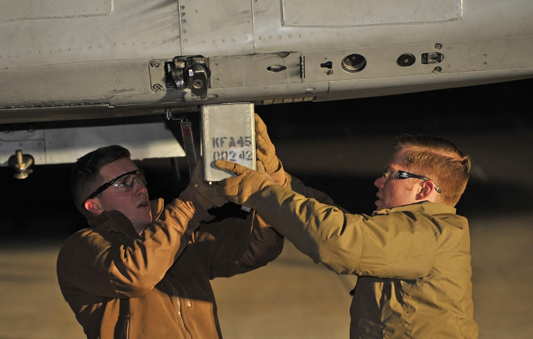 Senior Airman Jared Basham and Airman 1st Class Andrew Boyce, 9th Civil Engineer Squadron explosive ordnance disposal technicians, remove a magazine with a hung flare from an F-15 Eagle Feb. 6, 2017 at Kingsley Field, Oregon. A hung flare occurs when a flare doesn't properly fire. (U.S. Air Force photo/Airman Tristan D. Viglianco)