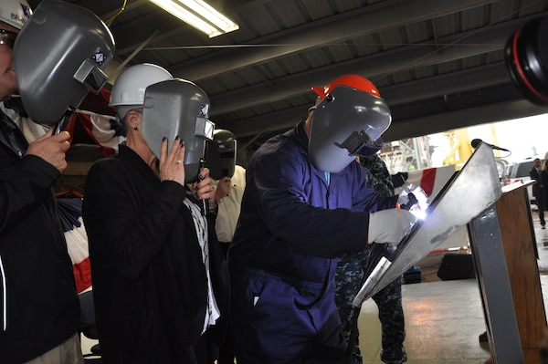 After tracing her initials onto the keel plate of DDG 121 -- the future USS FRANK E. PETERSEN, JR. -- Mrs. D'Arcy Neller, authenticator and ship sponsor, watches from behind a protective mask as Ingalls Shipbuilding structural welder Jeremy Lally etches her initials into the ship's keel plate.  The keel authentication ceremony for DDG 121 was held Tuesday morning, Feb. 21, at Ingalls Shipyard in Pascagoula, MS.  Also observing at left is Ingalls Shipbuilding President Mr. Brian Cuccias.  The keel's co-authenticator, Mr. Donald Brabston, a 50-year Ingalls employee, was unable to attend.