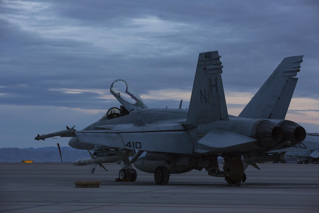 """An F/A-18C Hornet with Marine Fighter Attack Squadron (VMFA) 323 """"Death Rattlers"""" rests on the flight line prior to beginning night operations at Naval Air Station Fallon, Nev., Feb. 15. The Death Rattlers, one of two Marine Hornet squadrons to deploy aboard Navy aircraft carriers, trained at NAS Fallon to strengthen tactical air integration, fulfill predeployment requirements and build rapport with the Navy squadrons they will deploy with in summer 2017. (U.S. Marine Corps photo by Sgt. Lillian Stephens/Released)"""