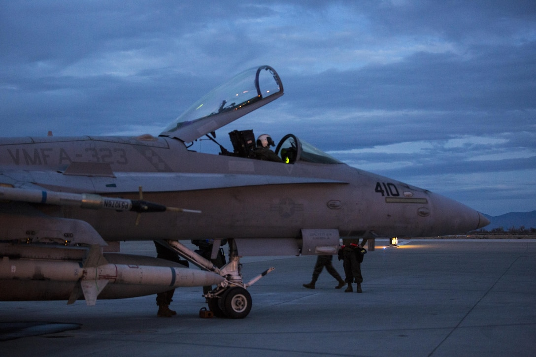 """The pilot of an F/A-18C Hornet with Marine Fighter Attack Squadron (VMFA) 323 """"Death Rattlers"""" inspects the aircraft's functions prior to beginning night operations at Naval Air Station Fallon, Nev., Feb. 15. The Death Rattlers, one of two Marine Hornet squadrons to deploy aboard Navy aircraft carriers, trained at NAS Fallon to strengthen tactical air integration, fulfill predeployment requirements and build rapport with the Navy squadrons they will deploy with in summer 2017. (U.S. Marine Corps photo by Sgt. Lillian Stephens/Released)"""