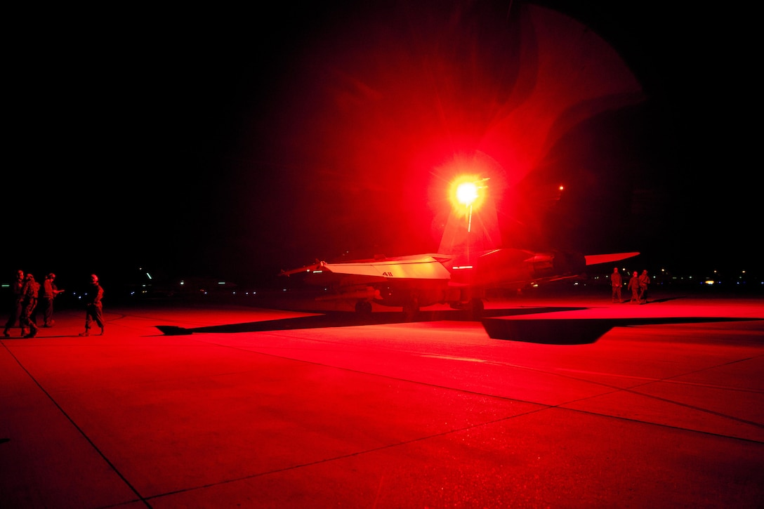 """An F/A-18C Hornet with Marine Fighter Attack Squadron (VMFA) 323 """"Death Rattlers"""" waits to conduct night operations at Naval Air Station Fallon, Nev., Feb. 15. The Death Rattlers, one of two Marine Hornet squadrons to deploy aboard Navy aircraft carriers, trained at NAS Fallon to strengthen tactical air integration, fulfill predeployment requirements and build rapport with the Navy squadrons they will deploy with in summer 2017. (U.S. Marine Corps photo by Sgt. Lillian Stephens/Released)"""