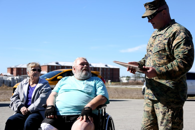 Chief Warrant Officer 3 Jason Alderman, right, reads an award certificate aboard Marine Corps Air Station Cherry Point, N.C., Feb 10, 2017, to James Tooker and his wife, Betty.  Tooker retired after 41 years as the station civilian fuel inspector.  Alderman is a bulk fuel officer with Headquarters and Headquarters Squadron, MCAS Cherry Point.  (U.S. Marine Corps photo by Cpl. Jason Jimenez/ Released)