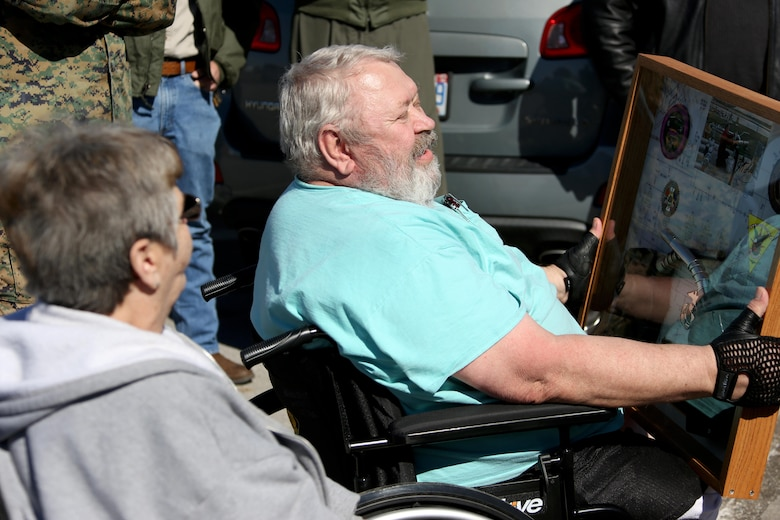 """James Tooker, right, admires a shadow box given in honor of his retirement aboard Marine Corps Air Station Cherry Point, N.C., Feb. 10, 2017.  A cookout was held in """"Jimmy's"""" honor during a retirement ceremony.  A U.S. Army veteran, Tooker formed a lasting bond with many of the Marines who worked in the department. (U.S. Marine Corps photo by Cpl. Jason Jimenez/ Released)"""