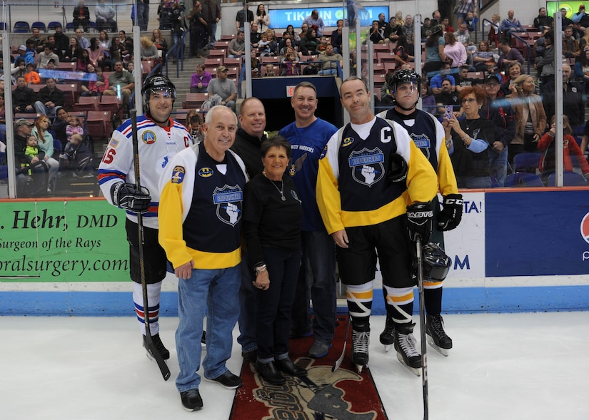 Members of the Charleston Patriots, the Charleston Enforcers and Col. Robert Lyman, center, Joint Base Charleston commander, poses for a photo with the Matuskovic family after dropping the puck during the 3rd Annual Matuskovic Charity Hockey Game at the North Charleston Coliseum & Performing Arts Center, Feb. 18, 2017. The game is played in memory of Joe Matuskovic, Charleston County Sherriff's deputy and other service members and first responders killed in the line of duty. Members of the Charleston Patriots are from Joint Base Charleston while members of the Charleston Enforcers are from the Charleston County Sheriff's office and fire department.