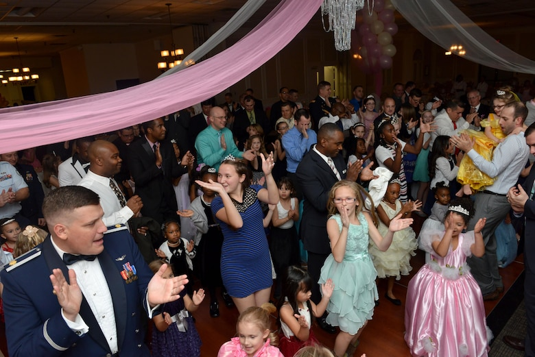 "Team Shaw members clap their hands while dancing during a ""Royal Affair"" father-daughter princess ball at Shaw Air Force Base, S.C., Feb. 18, 2017. More than 100 couples signed up for the dance, which included entertainment, dinner and activities such as musical chairs. (U.S. Air Force photo by Airman 1st Class Destinee Sweeney)"