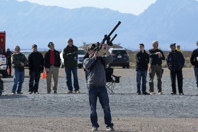 Justin Simpson, a member of the Kirtland Air Force Base team, aims a signal-jamming device at an unmanned aerial system as judges and range personnel watch Dec. 12 during the 2016 Air Force Research Laboratory Commander's Challenge at the Nevada National Security Site near Las Vegas, Nevada. Teams were given six months to develop a complete system to aid in base defense. Kirtland's system is able to detect, identify and track unmanned aerial systems with the capability of engaging through signal jamming and capture using a net gun.