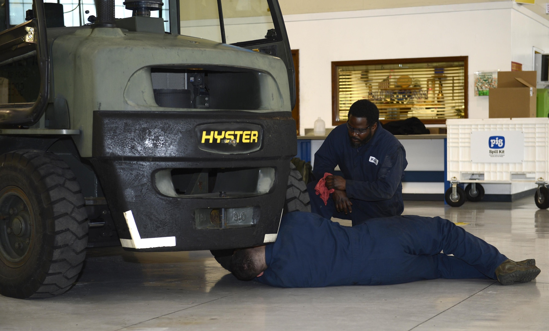 Walter Wilson and U.S. Air Force Airman 1st Class Nicholas Imber, 733rd Logistics Readiness Squadron vehicle maintainers, use a grease gun to squeeze bio-based grease into a forklift carriage at Joint Base Langley-Eustis, Va., Jan. 31, 2017. JBLE is one of four Air Force bases that will perform a 12-month long test of the grease on its vehicles. (U.S. Air Force photo by Airman 1st Class Kaylee Dubois)