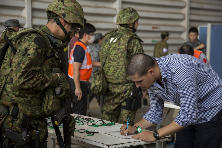 A Japan Air Self-Defense Force member helps process a role player during a noncombatant evacuation operation, as part of Cobra Gold 17 at Naval Airbase Utapao, Thailand, Feb. 19, 2017. The drill was conducted to exercise joint, multinational cooperation during disaster relief. Cobra Gold is the largest Theater Security Cooperation exercise in the Indo-Asia-Pacific region and is an integral part of the U.S. commitment to strengthen engagement in the region. U.S., Thai, Malaysian and Japanese forces participated in the disaster relief drill.