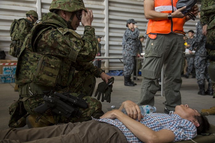 A Japan Air Self-Defense Force member tends to a role player during a noncombatant evacuation operation, as part of Cobra Gold 17 at Naval Airbase Utapao, Thailand, Feb. 19, 2017. The drill was conducted to exercise joint, multinational cooperation during disaster relief. Cobra Gold is the largest Theater Security Cooperation exercise in the Indo-Asia-Pacific region and is an integral part of the U.S. commitment to strengthen engagement in the region. U.S., Thai, Malaysian and Japanese forces participated in the disaster relief drill.