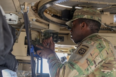 Army Pfc. Oluwemimo Alenbayo, a signal support systems specialist attached to 1st Squadron, 73rd Cavalry Regiment, 2nd Brigade Combat Team, 82nd Airborne Division, fills an Advanced System Improvement Program tactical radio in a vehicle at Qayyarah West Airfield, Iraq, Feb. 9, 2017. The brigade conducted a communications exercise in preparation for the upcoming Iraqi security forces offensive into West Mosul. Army photo by Staff Sgt. Jason Hull