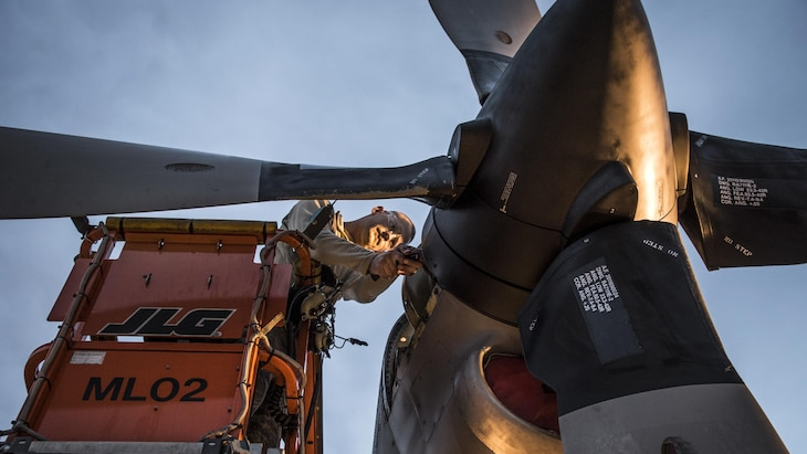 An airman works on the engine of a C-130H Hercules as the sun rises over the 179th Airlift Wing in Mansfield, Ohio, Feb. 21, 2017.  Air National Guard photo by 1st Lt. Paul Stennett