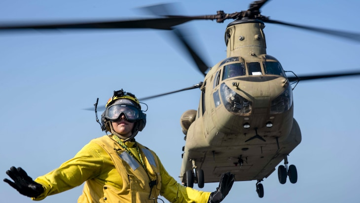 Navy Petty Officer 3rd Class Julia Valles signals as an Army CH-47F Chinook takes off from the USS Green Bay near Thailand, Feb. 21, 2017. Navy photo by Petty Officer 1st Class Chris Williamson