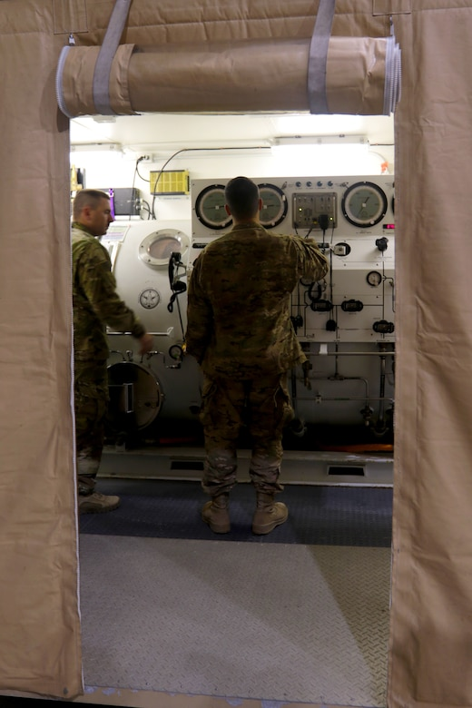 Master diver 1st Sgt. Tyler Dodd with the 511th Engineer Dive Detachment out of Fort Eustis, Va., oversees training of Standard Navy Double Lock Recompression Chamber System while salvage diver Spc. Nathaniel Marquez works the control console, Kuwait Naval Base, Kuwait, Feb. 13, 2017. The training is to give 511th Soldiers hands on training in equipment operation, Soldier advancement and to help a Soldier with an injury sustained during a previous training exercise.