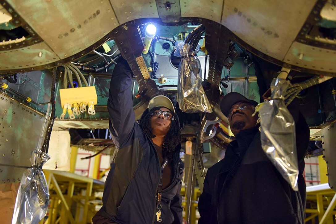 Tanya Thompson, 561st Aircraft Maintenance Squadron aircraft worker, and Alvin Abraham, 561st AMXS aircraft hydraulic systems technician, install hydraulic lines in the airframe mounted accessory drive area of an F-15 during depot maintenance Feb. 16, 2017, at Robins Air Force Base. (U.S. Air Force photo by Tommie Horton/Released)