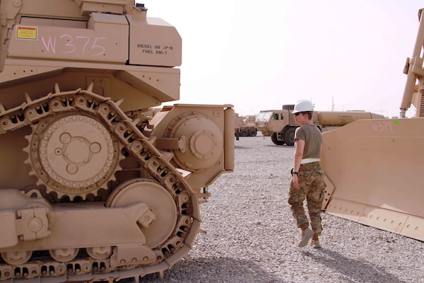 Army Staff Sgt. Jenna Vaughn, 1st Theater Sustainment Command's Iraq Train and Equip Funding noncommissioned officer, inspects bulldozers received for ITEF July 12, 2016 in Southwest Asia. Armored bulldozers such as these were provided through DLA Troop Support's Heavy Equipment Procurement Program and will allow Iraqi combat engineers to more effectively clear convoy routes of roadside bombs and other threats in the ongoing fight against the Islamic State of Iraq and the Levant.